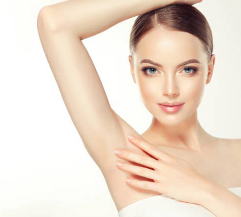 Gorgeous, young, brown haired woman with clean fresh skin and hair gathered in neat hairstyle is touching tenderly clean shaved armpit. Soft make up and light smile on the perfect face. Depilation, cosmetology and beauty technologies.